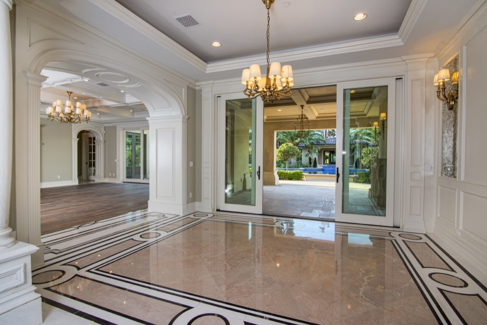 Shiny marble floors and French doors leading to garden in estate built by Richard Smith Custom Home Development
